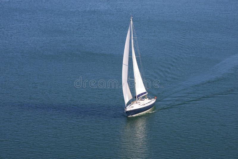 Einzelne Yacht auf blauem Meer stockfotos