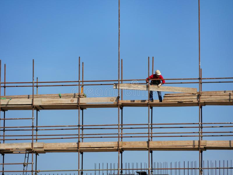 Einzelner Bauarbeiter auf Baustellebaugerüst stockfotografie