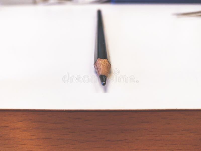 Einzelner Bleistift auf einer weißen Tabelle mit hölzerner Seitenkonsole stockfotografie