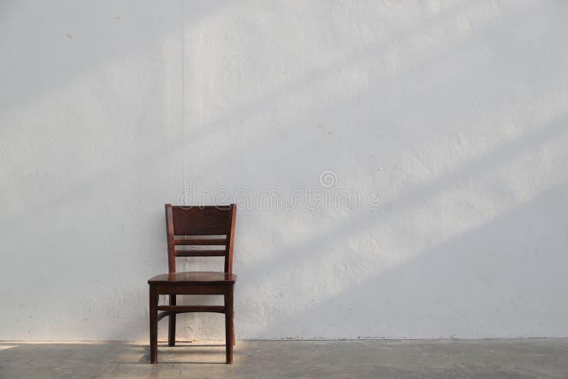 Einzelner brauner Holzstuhl mit hellem Strahl vom Fenster auf weißem Wandhintergrund stockfoto