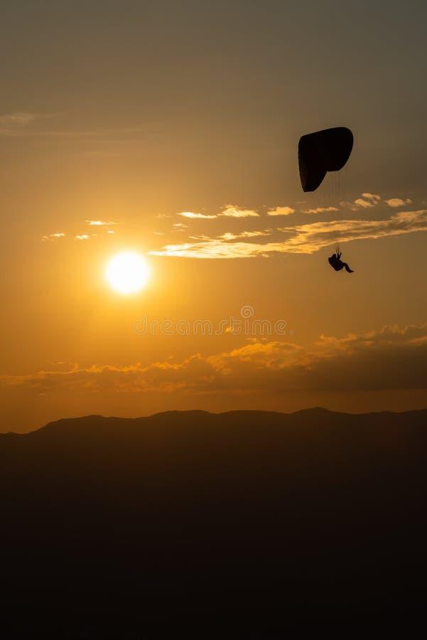 Einzelner Gleitschirm, der in Richtung zur Stadt von Genf bei Sonnenuntergang absteigt lizenzfreie stockfotos