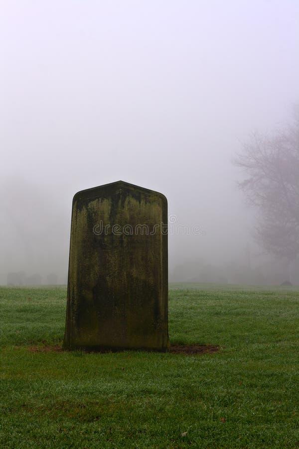 Einzelner Grabstein in einem gespenstischen Friedhof stockbilder