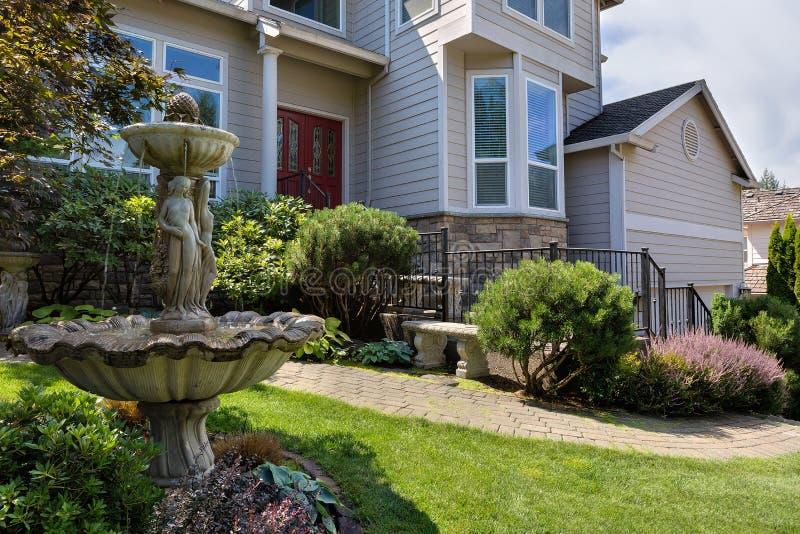 Einzelner Hauptfrontyard mit manikürtem Garten und grünem Rasen lizenzfreie stockfotografie