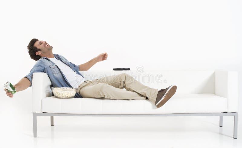 Einzelner Mann auf der Couch Fernsehend lizenzfreie stockfotografie