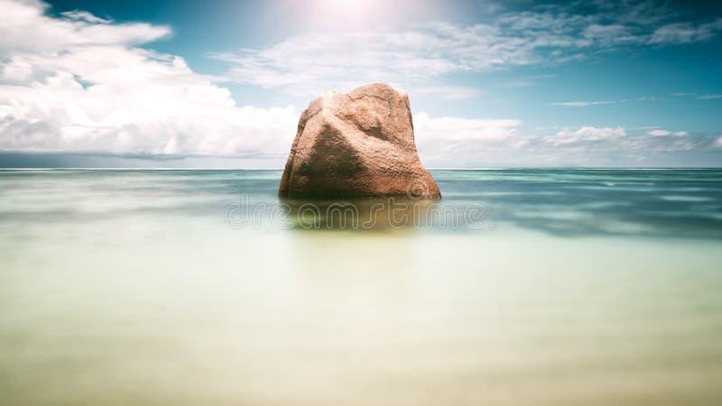 Einzelner Steinfelsen im Meer unter Sonne Leerer See- und Strandhintergrund mit Kopienraum, lange Belichtung, Unschärfebewegung stockfoto