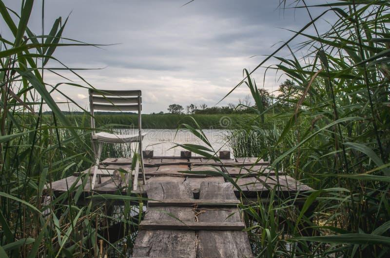 Einzelner Stuhl auf alter Holzbrücke auf dem See, bewölkter Tag stockbild
