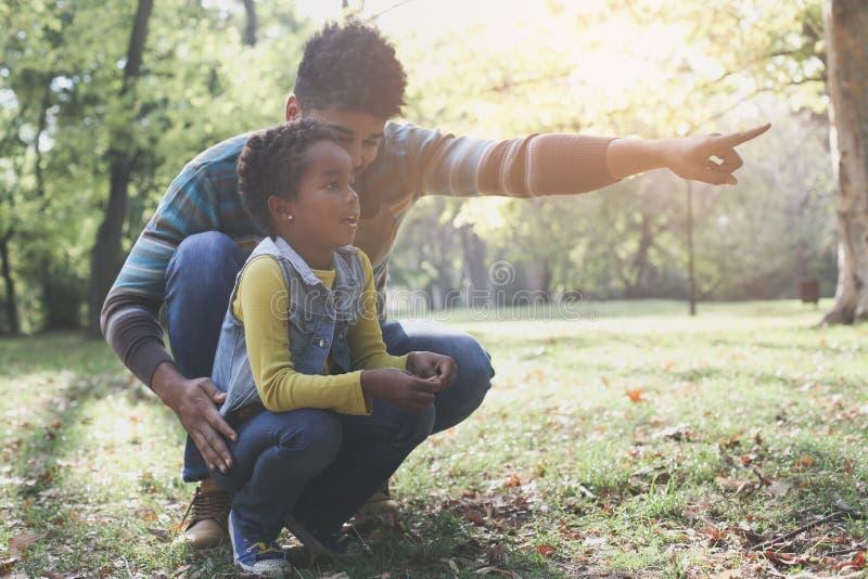 Einzelner Vater des Afroamerikaners, der seiner Tochter etwas zeigt stockbild