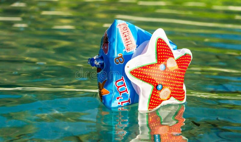 Einzelnes aufblasbares Armfloss auf Wasser mit Reflexion stockfoto