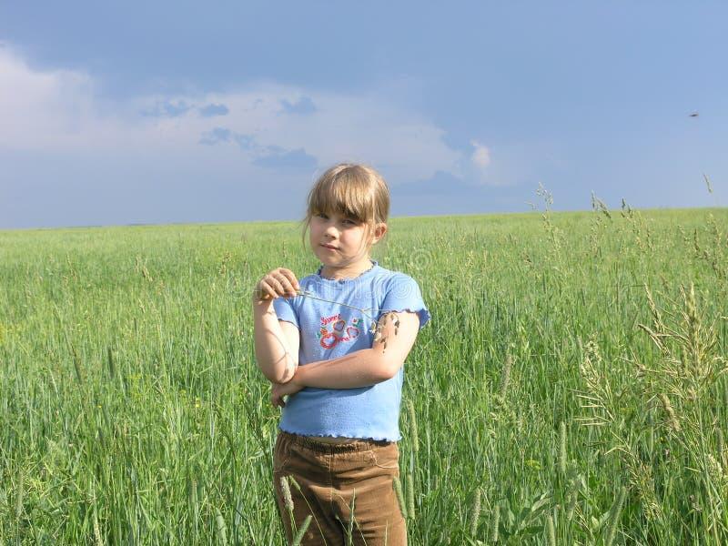 Einzelnes Kind unter dunklem Sturmhimmel stockfotografie
