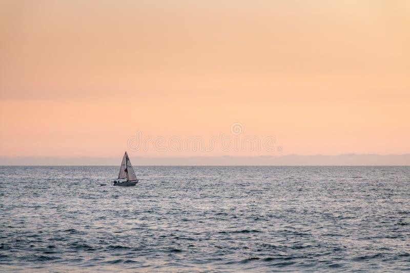 Einzelnes Segelbootssegeln auf Meer während eines orange Sonnenuntergangs lizenzfreie stockfotos