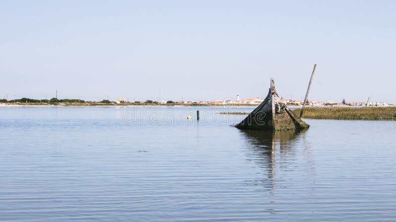 Einzelnes und einsames versunkenes Boot halb-versenkte in die Mündung von Aveiro-Lagune, Portugal Kleine wunderliche Stadt im Hor lizenzfreie stockfotos