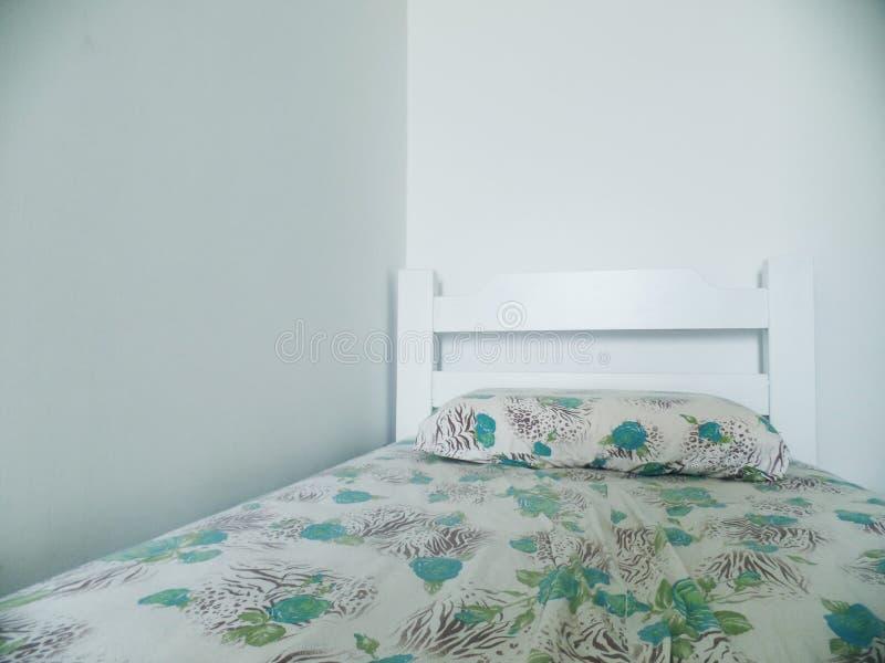 Einzelnes weißes Bett mit Blumenstempeln lizenzfreie stockfotos