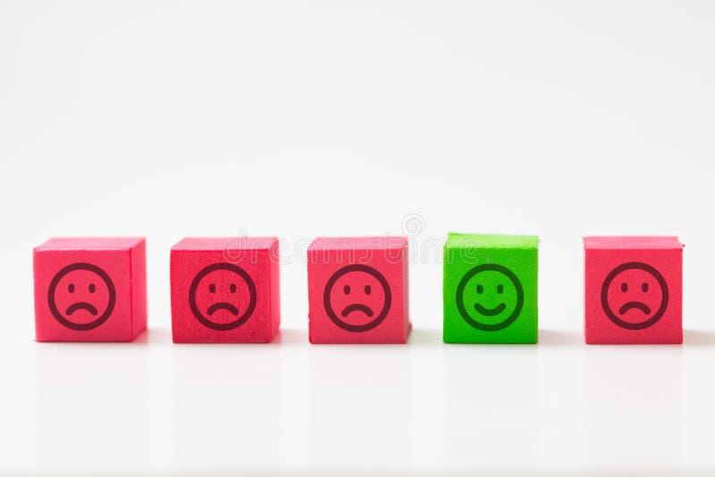 Einzigartig, optimistisch, Glück, Unterschiedkonzept unter Verwendung des einzelnen glücklichen Gesichtes unter vielen traurigen  stockfoto
