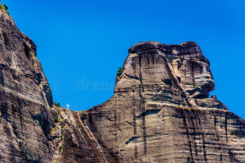 Einzigartige Form gebildet durch Hügel und weißes Kreuz der Heiliger Dreifaltigkeit am meteora Griechenland lizenzfreies stockbild