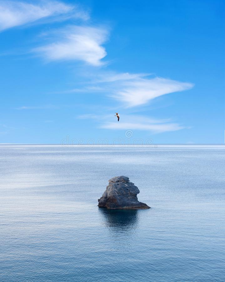 Einziger Felsen über ruhigem See und Fliegenvogel über blauem Himmel lizenzfreie stockbilder