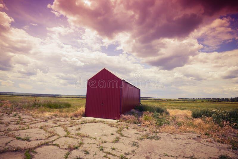 Einziger roter Hangar auf dem verlassenen Flugplatz lizenzfreies stockfoto
