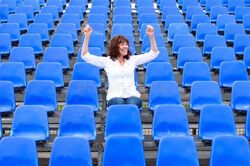 Einziges weibliches sitzendes Zujubeln des Fans oder des Zuschauers stockbilder