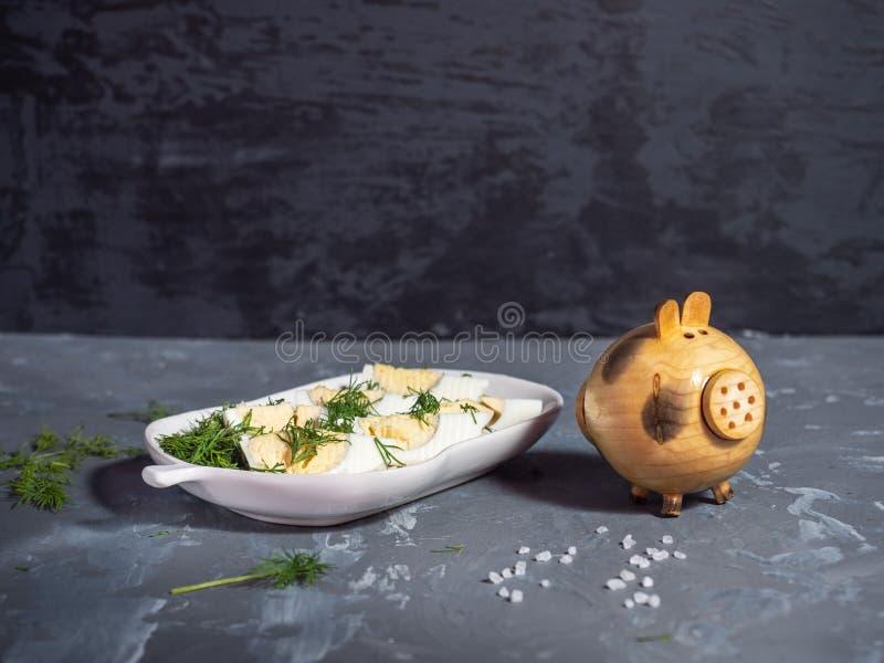 Eiplakken met gehakt dille en zout worden bestrooid dat Decoratief houten zout schudbekervarken Groot zout op een schotel in de v stock foto's