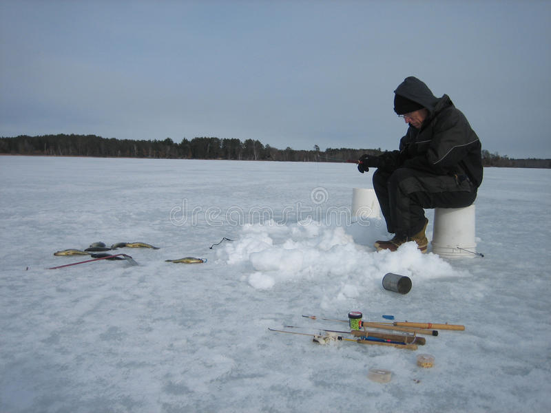Eis-Fischen auf einem gefrorenen See lizenzfreie stockfotografie