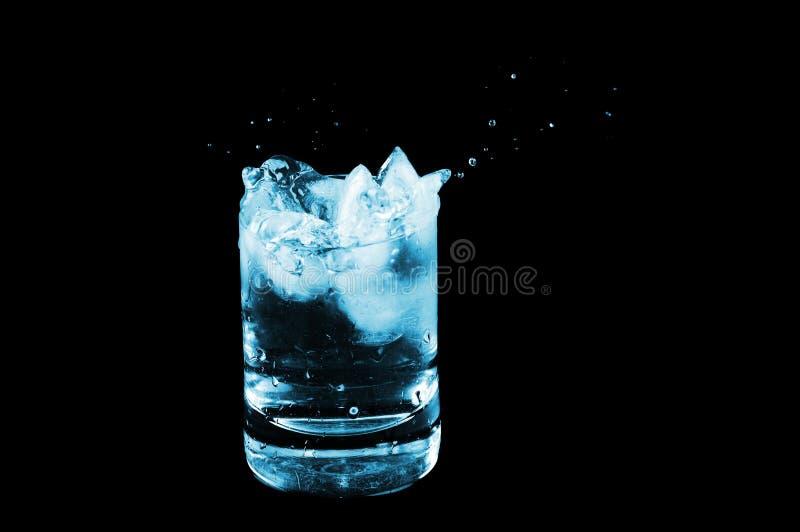 Eis im Glas und Wasser spritzt getrennt auf Schwarzem stockfoto
