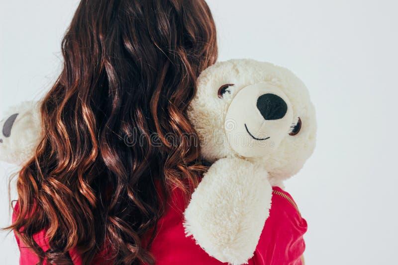 Eisbärspielzeug umarmt junge gelockte brunette Frau im hellen rosa Kleid stockfotografie