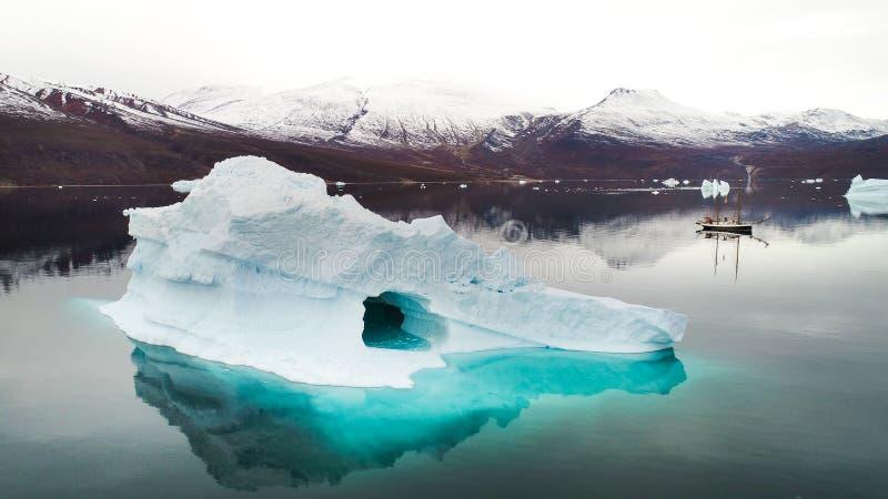 Eisberg mit Segelboot in Grönland stockbild