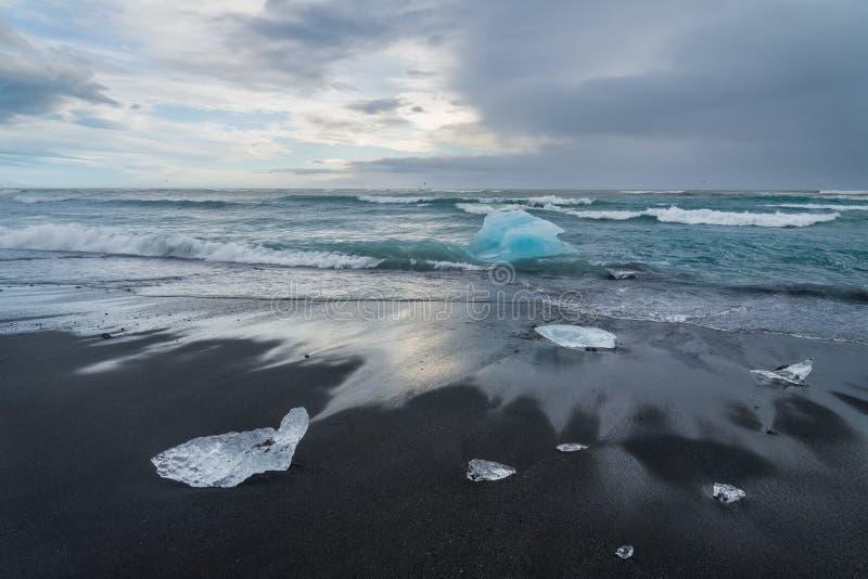 Eisberge auf einem schwarzen Sand Jokulsarlon setzen, Island auf den Strand lizenzfreie stockfotos