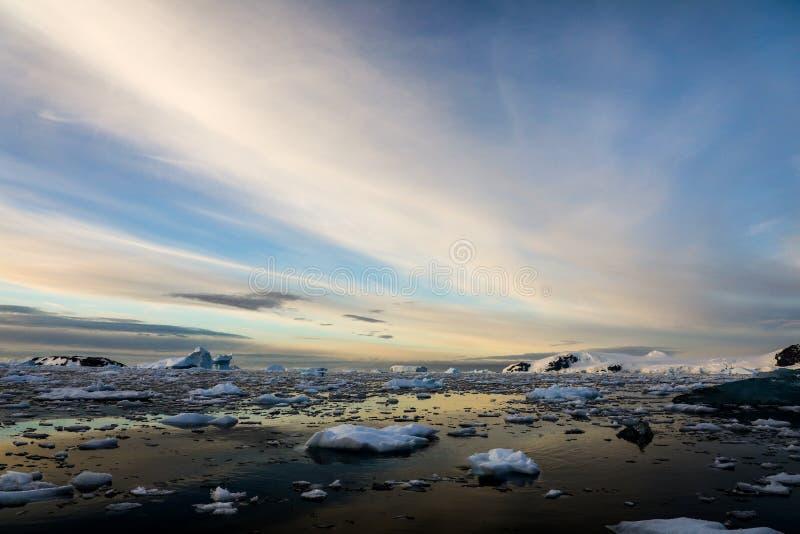 Eisberge, die in den Ozean gegen einen drastischen blauen und bewölkten Himmel, die Antarktis schwimmen lizenzfreie stockfotos