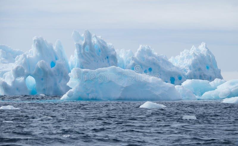 Eisberge mit Löchern in einem Abstand lizenzfreie stockbilder