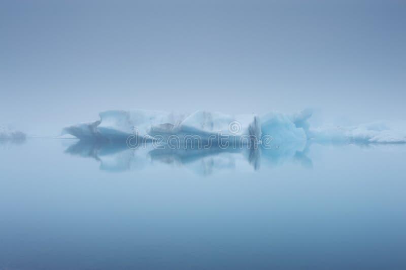 Eisberge und ihre Reflexionen in einem Nebel, Jokulsarlon, Island stockfoto