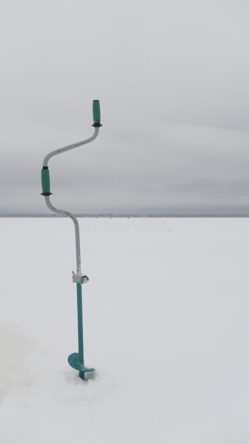 Eisbohrer auf dem See Ausrüstung für die Winterfischerei lizenzfreie stockfotos