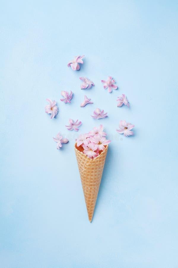 Eiscreme des rosa Fliegens blüht im Waffelkegel auf Draufsicht des blauen Pastellhintergrundes Schöne Blumenzusammensetzung, flac stockfotografie