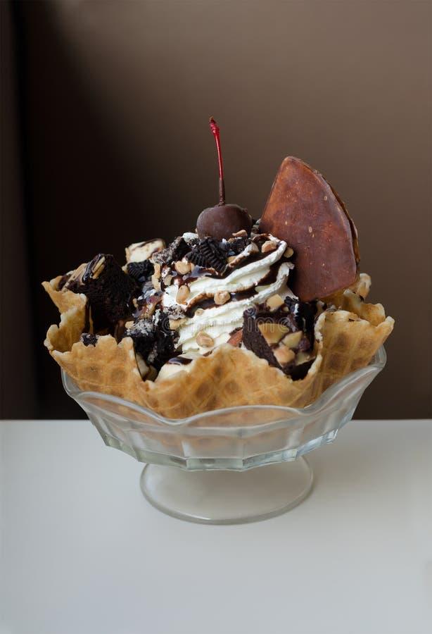 Eiscreme-Eiscremebecher in einer essbaren Waffelschüssel mit Schokoladenkuchen, Mandeln lizenzfreie stockfotografie