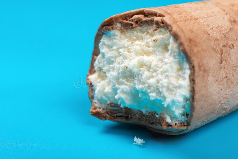 Eiscremerolle mit äußerem Abschluss der Schokolade oben auf Blau stockbild