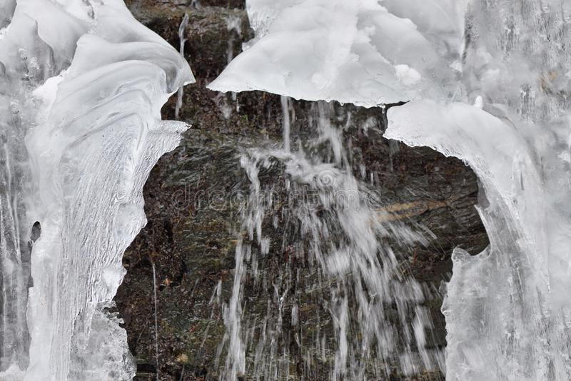 Eiseiszapfen hängen an den Gebirgsfelsen an einem kalten Wintertag mit wat lizenzfreie stockfotografie