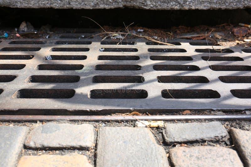 Eisen-Sturm-Abfluss mit Ziegelsteinen und Rückstand lizenzfreie stockbilder