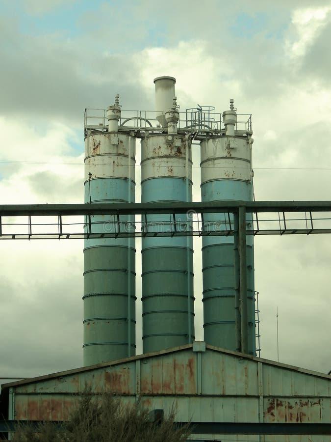 Eisen-Zisternen auf der alten konkreten Fabrik stockbild