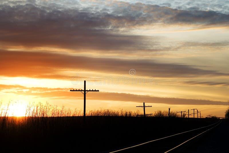 Eisenbahn nahe bei den alten Telefonmasten bei Sonnenuntergang stockbild