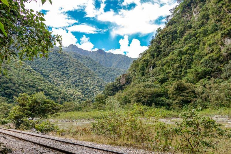 Eisenbahn zur Inkazitadelle Machu Pichhu und peruanische Berge am sonnigen Tag lizenzfreie stockfotografie