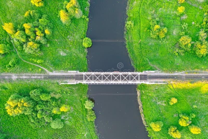Eisenbahnbrücke unter grünen Wiesen über einem kleinen Fluss in der Landschaft, Vogelperspektive lizenzfreie stockbilder