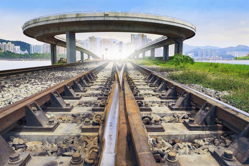 Eisenbahnlinie und Brücke kreuzen vorbei mit städtischer Szene hinter Gebrauch stockbilder