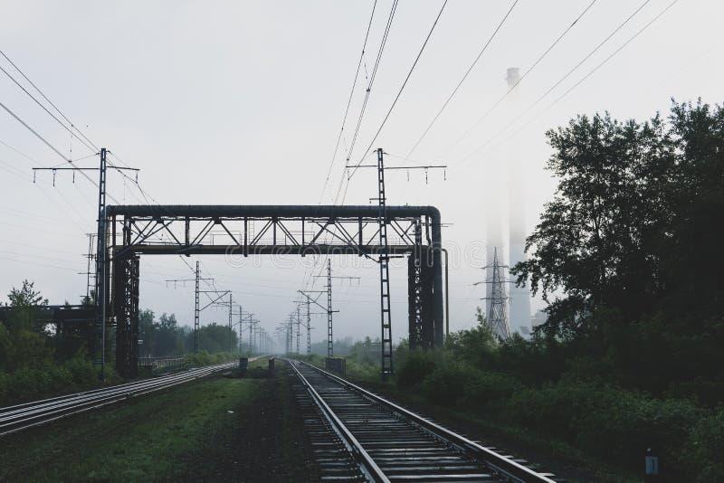 Eisenbahnlinien, die in den Nebel, in die Rohrleitungen und in die Kamine im Dunst einsteigen lizenzfreie stockbilder