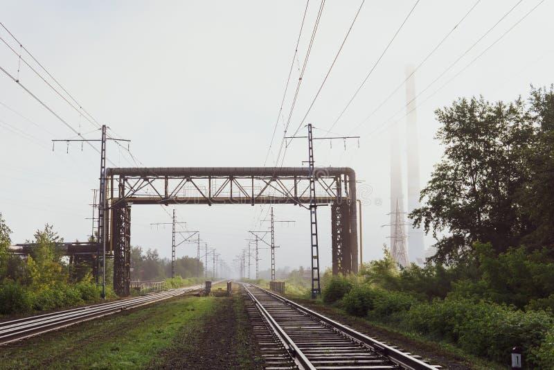 Eisenbahnlinien, die in den Nebel, in die Rohrleitungen und in die Kamine im Dunst einsteigen stockbild