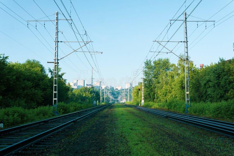 Eisenbahnlinien, die zu die Stadt auf einem Hügel im Abstand führen stockfotografie