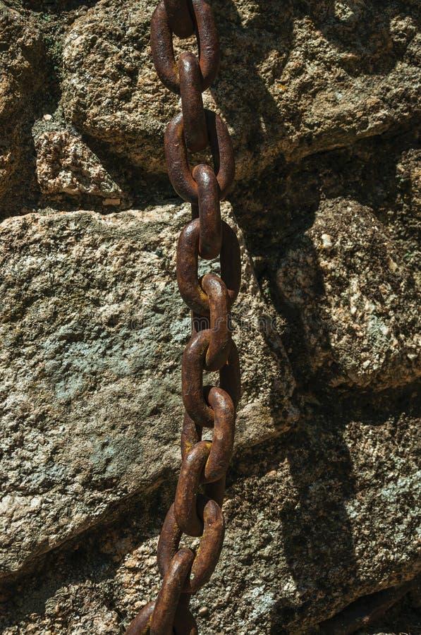 Eisenkette gehaftet in einer Steinbacksteinmauer stockbilder