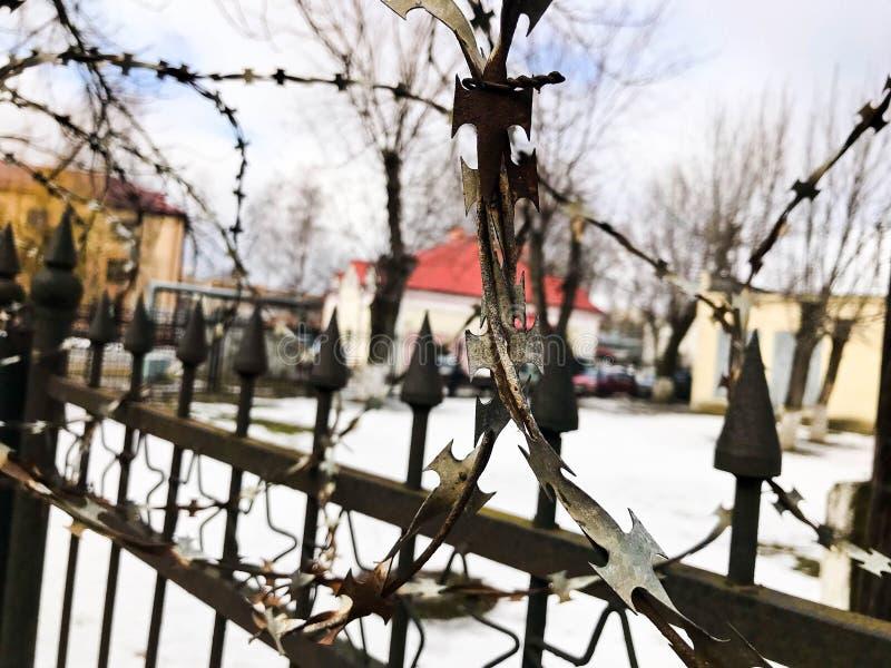Eisenmetallscharfer gefährlicher schützender Stacheldraht auf dem Zaun mit Spitzen und Stangen gegen den Himmel lizenzfreie stockbilder