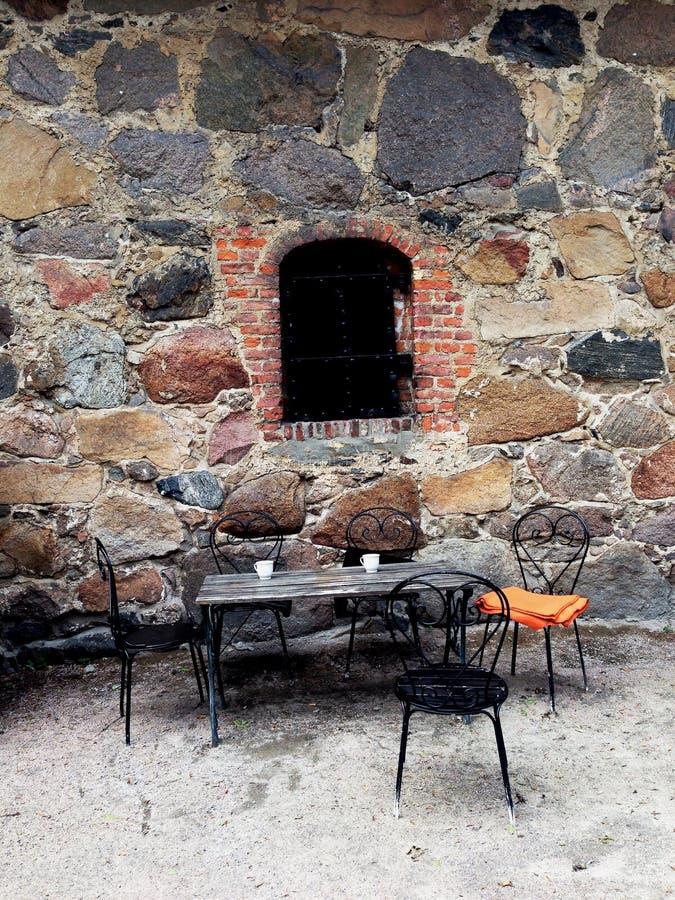 Eisenstuhl und -tabelle außerhalb des Altbaus lizenzfreies stockfoto