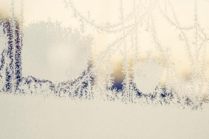 Eisgefrorenes auf einem Fenster im Sonnenaufgang stockbild