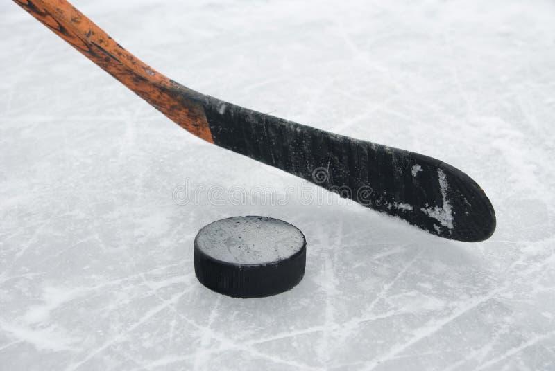 Eishockeysteuerknüppel und -kobold auf Eis stockbild