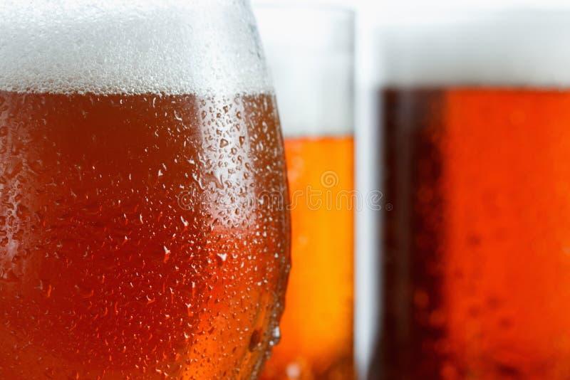 Eisige Gläser kühles Bier schäumen, bedeckt mit Tropfen, Nahaufnahme lizenzfreies stockfoto